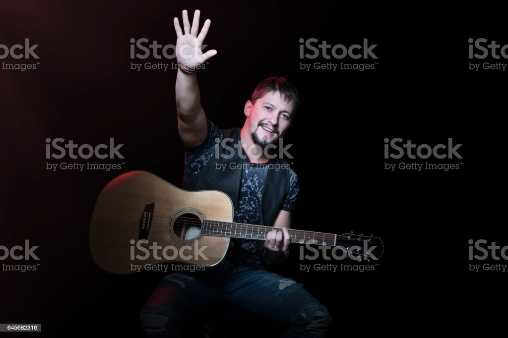 Guitarist with his hand raised stock photo