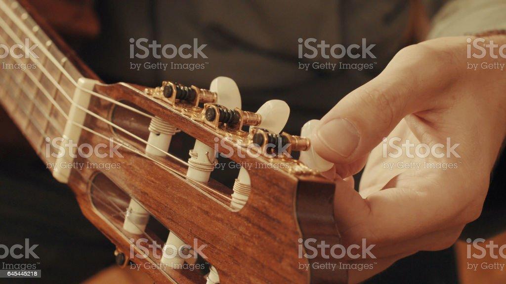 Guitarist's hands tuning guitar stock photo