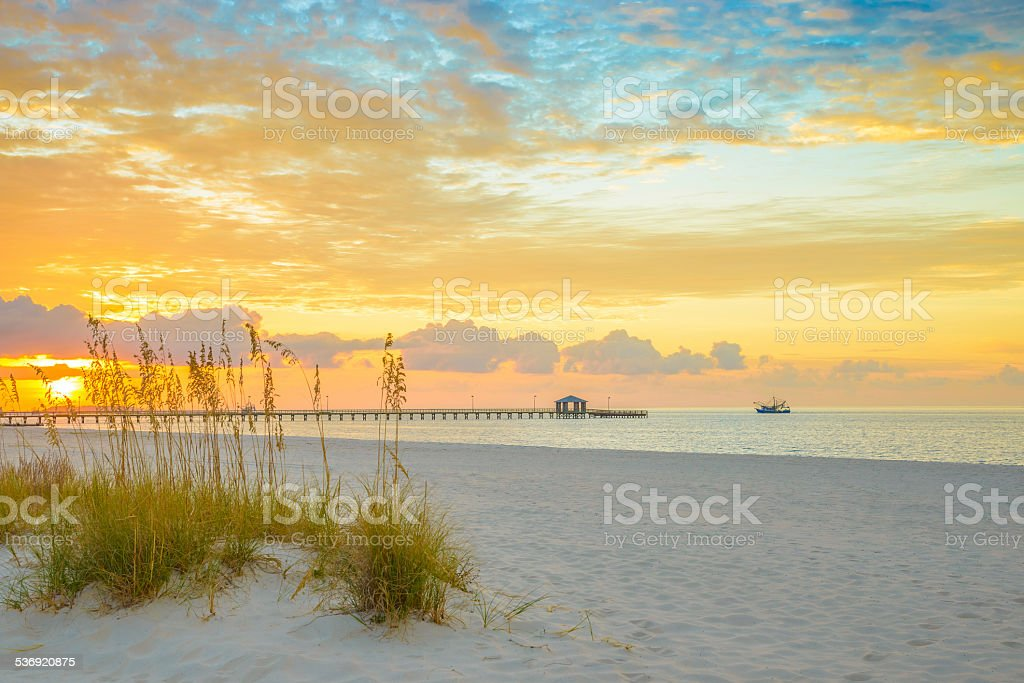 Gulfport Mississippi beach, dramtic golden sunrise, pier, shrimp boat, bay stock photo