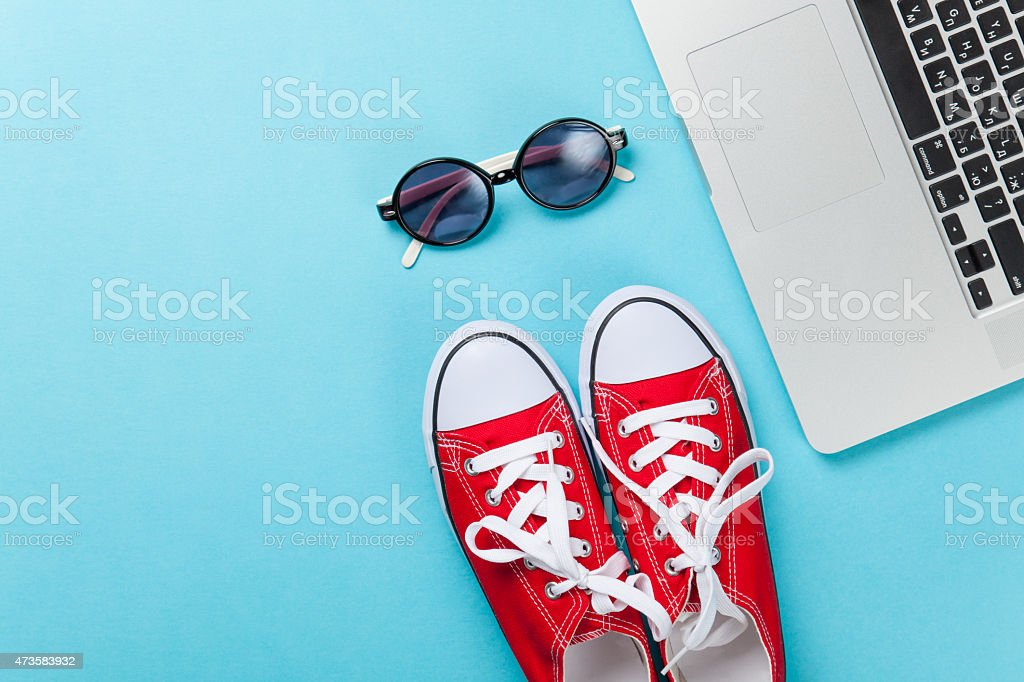 gumshoes and laptop near sunglasses stock photo
