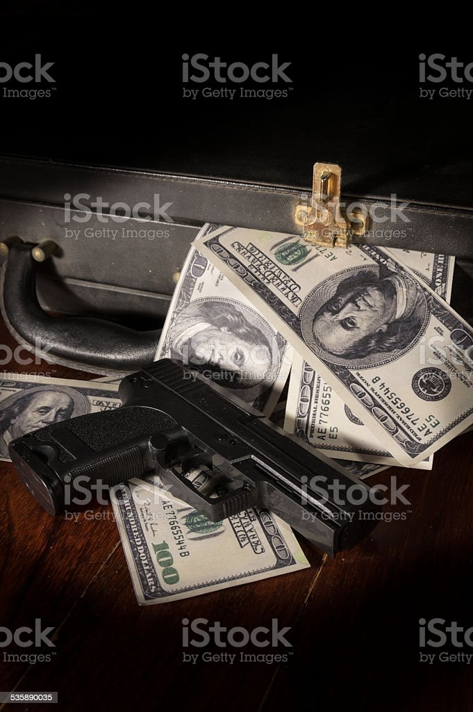 Gun and dollar bill in briefcase. stock photo