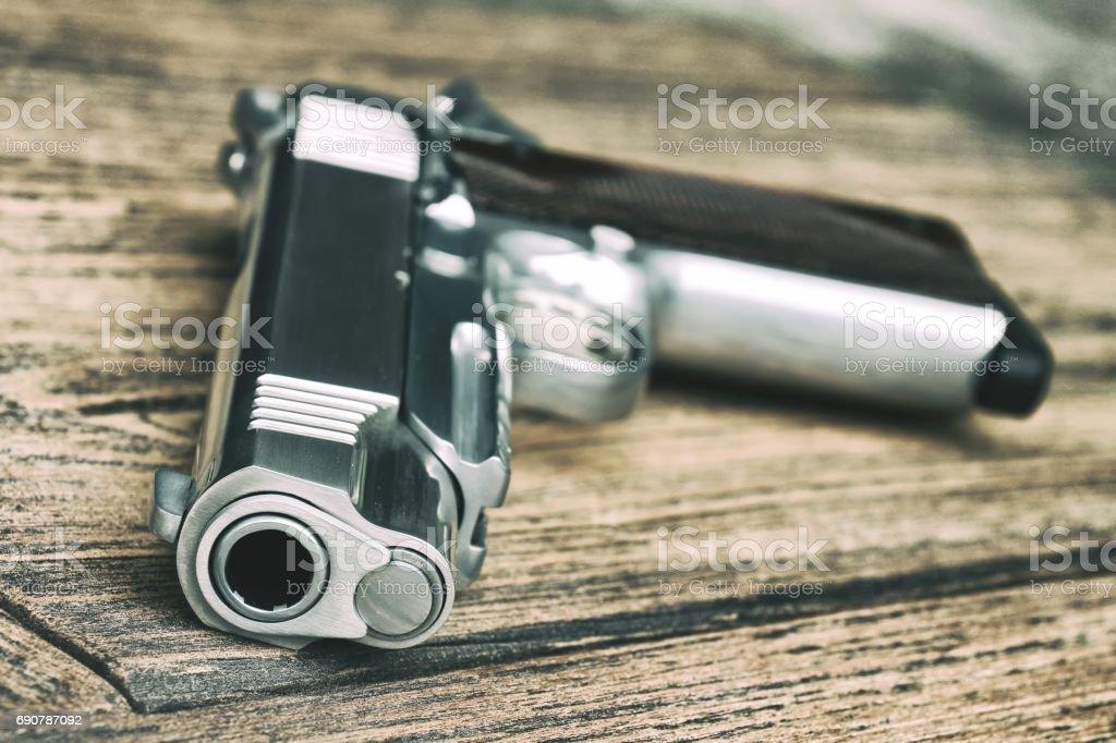 Gun Barrel, 1911 Model, Semi-automatic handgun on wooden background, .45 pistol, Close-up Barrel. stock photo