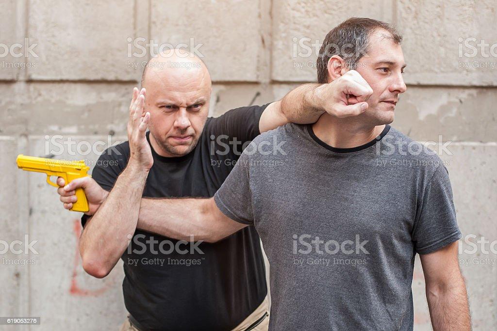 Gun Disarm. Self defense techniques against a gun point. stock photo
