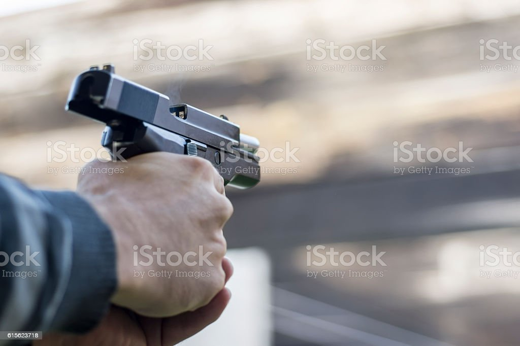Gun Fire Street Assault. Shooting a Handgun and Smoke. stock photo