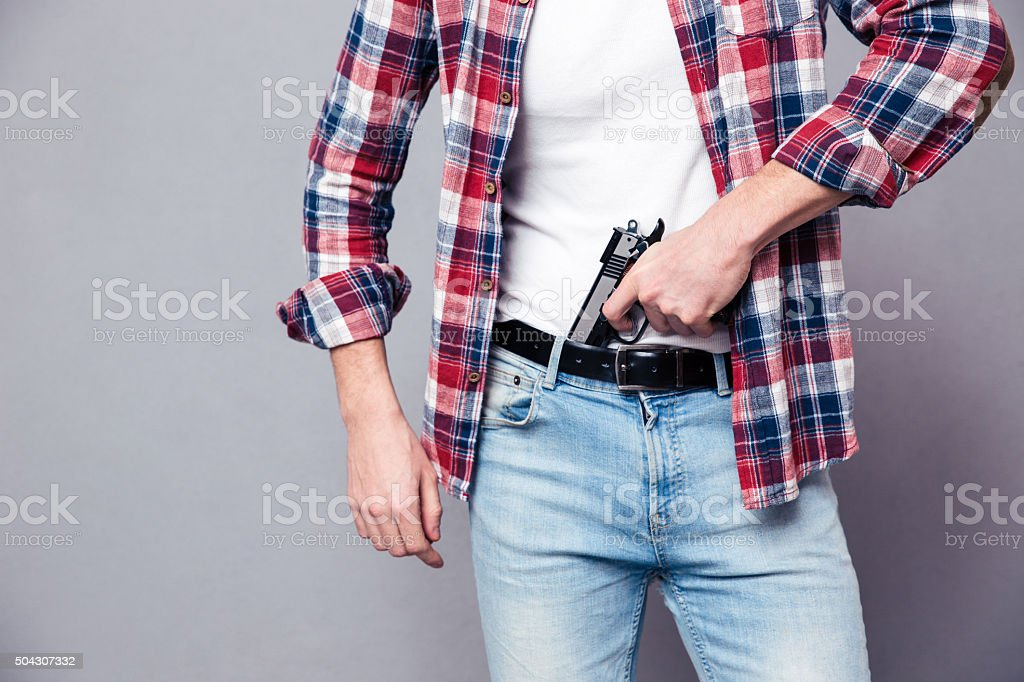 Gun holded by hands of strong young man stock photo
