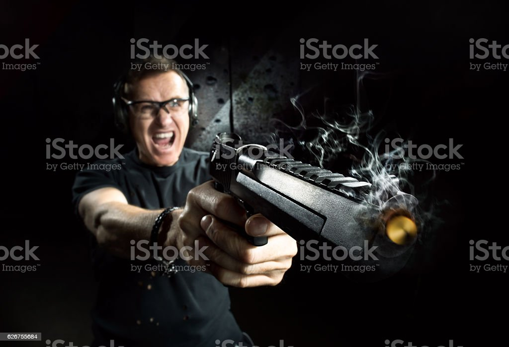 Gun in the hands of the man stock photo