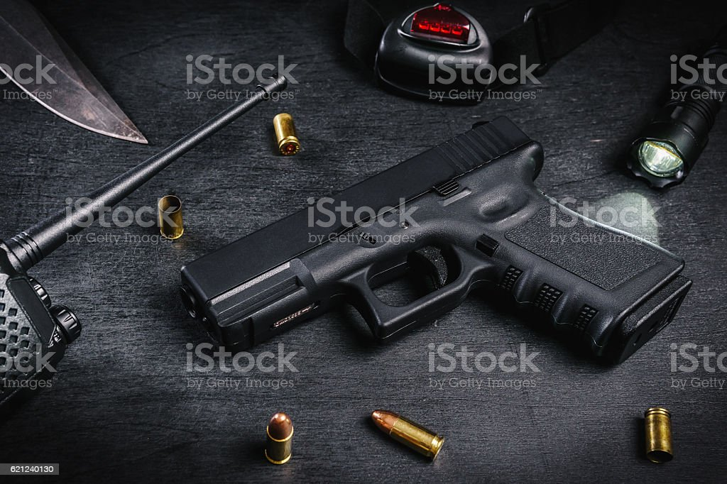 gun, knife and cartridges on a black table stock photo