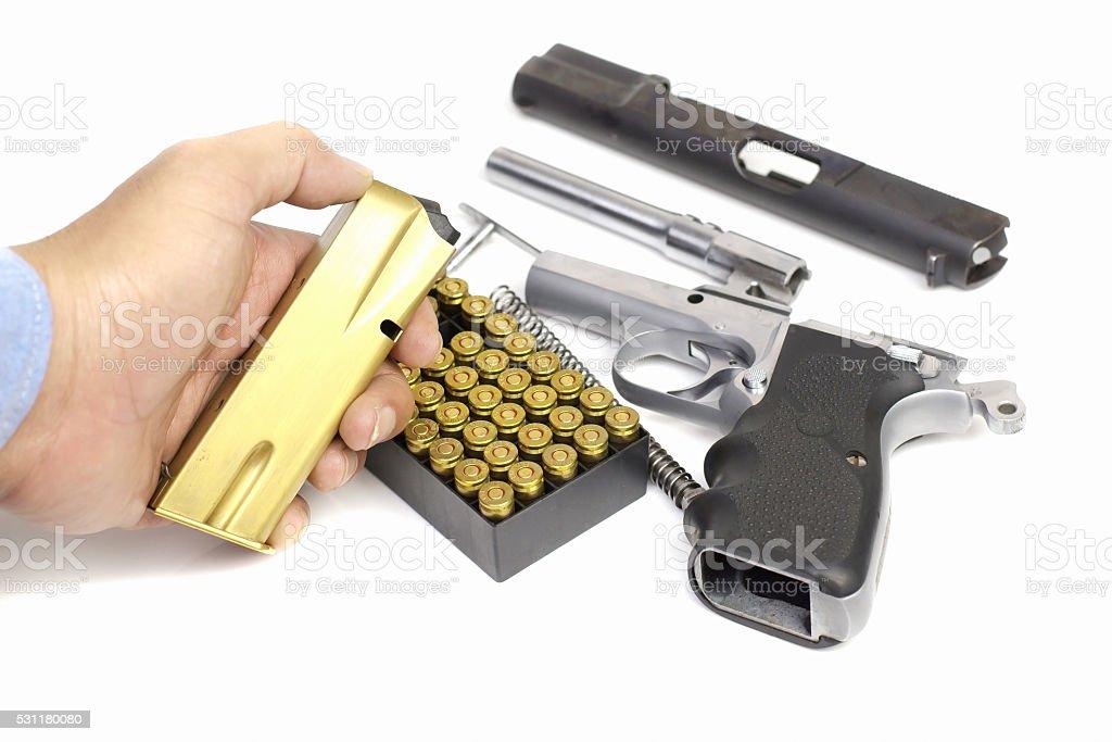Gun magazine on hand, bullets, Disassembled handgun, Isolated. stock photo