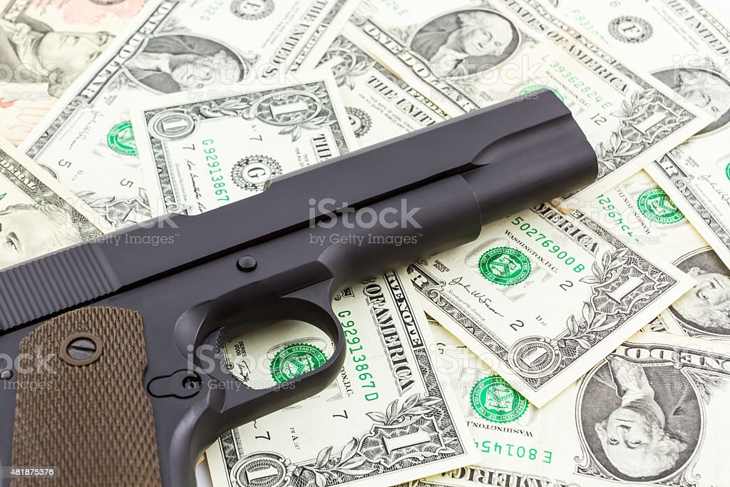 Gun on money texture background. stock photo