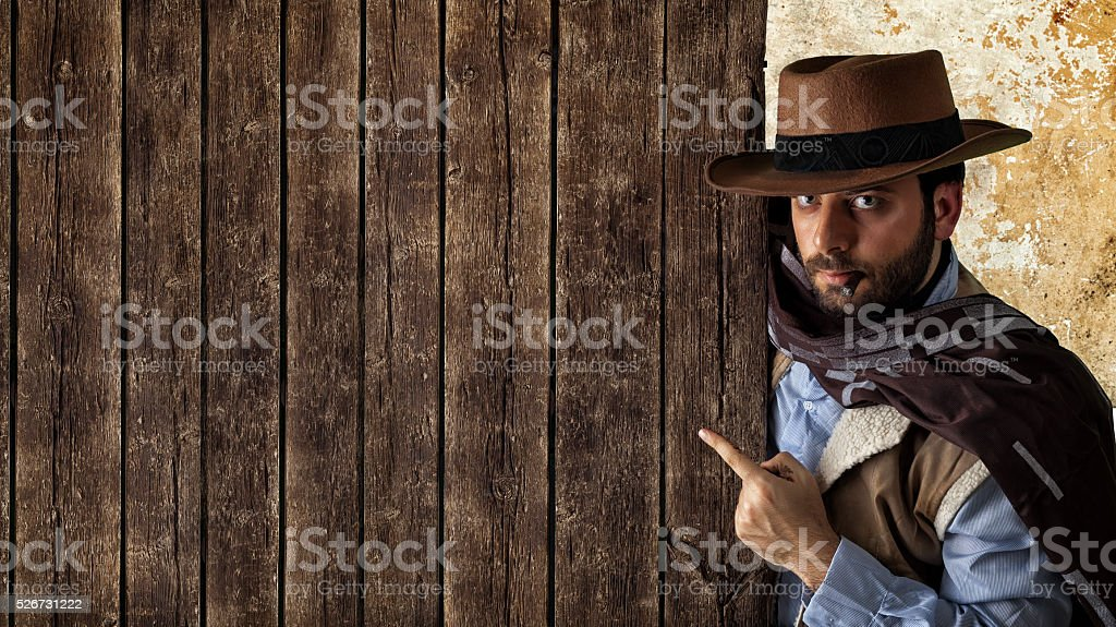 Gunfighter pointing on wooden table. stock photo