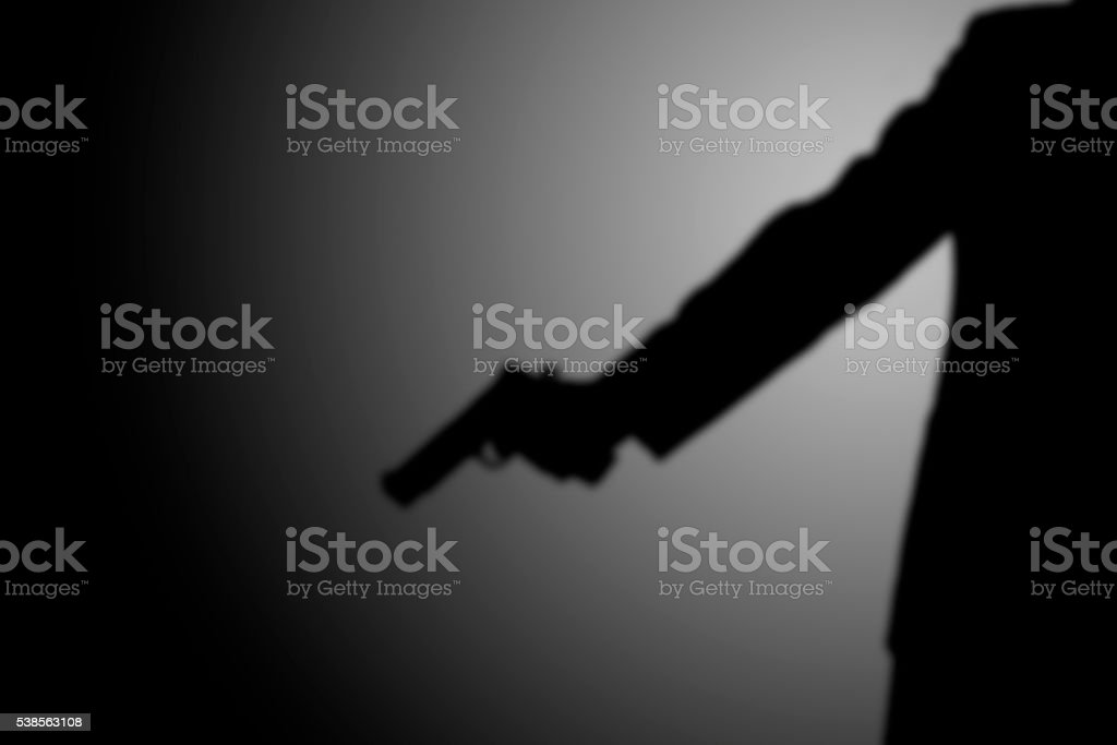 gunman killer shooting. light and shadow stock photo