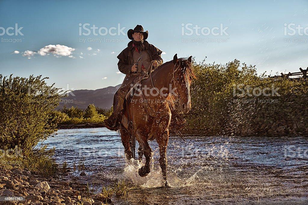 Gunslinger On Horseback Riding In The Riverbed royalty-free stock photo