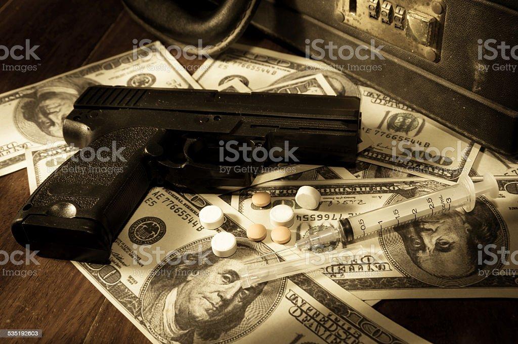 Gun,syringe and pills on dollar bills. stock photo