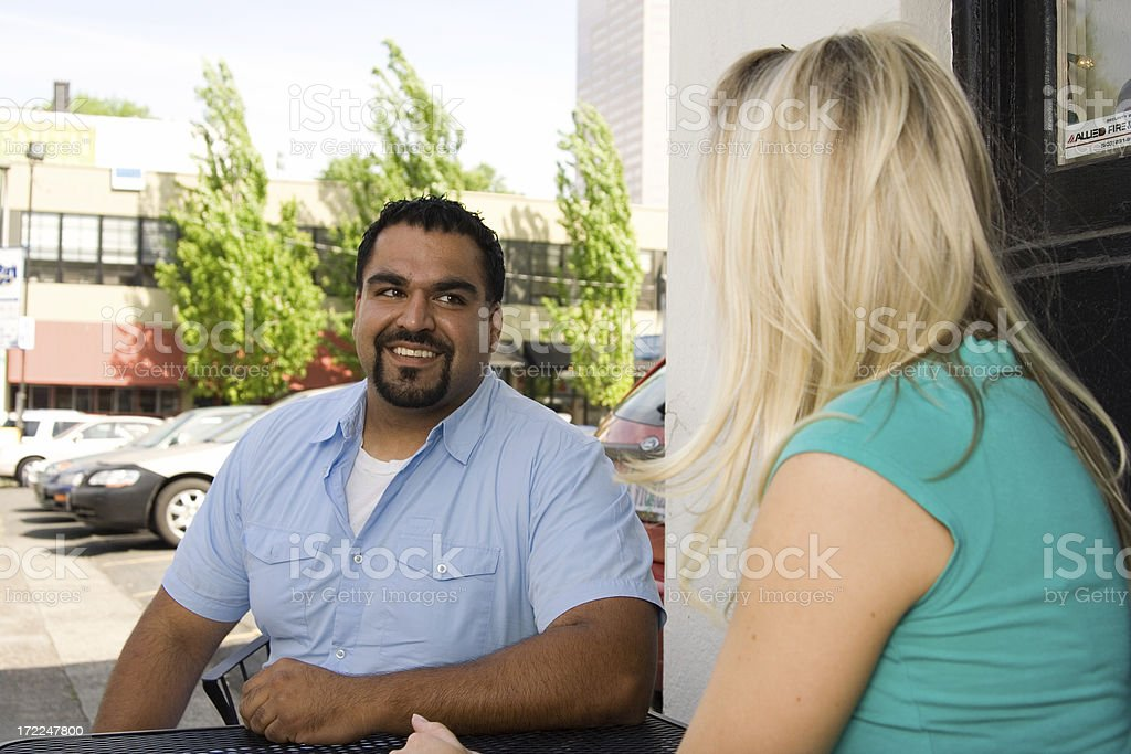 guy and girl at a table talking royalty-free stock photo