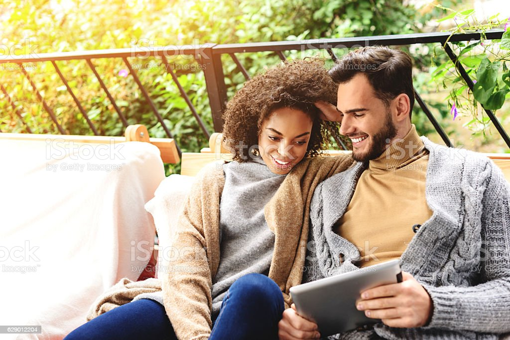 guy and girl relaxing on a terrace stock photo
