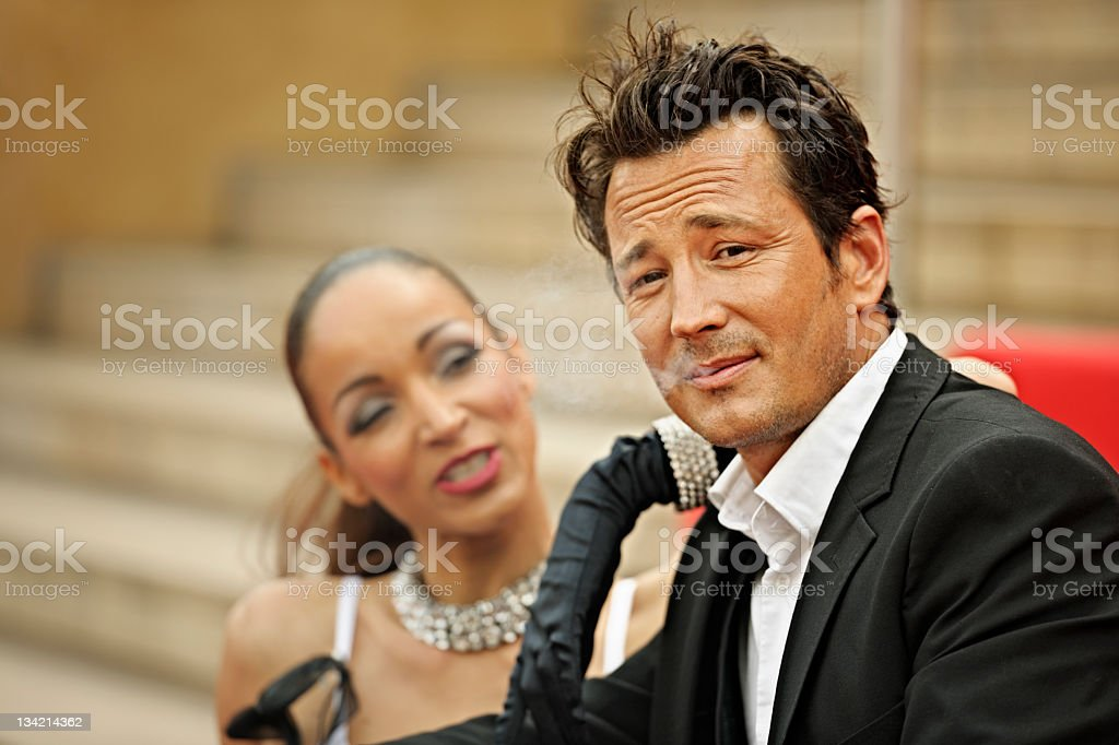 Guy and his Doll, Tanned Man Smoking with Latin Woman royalty-free stock photo