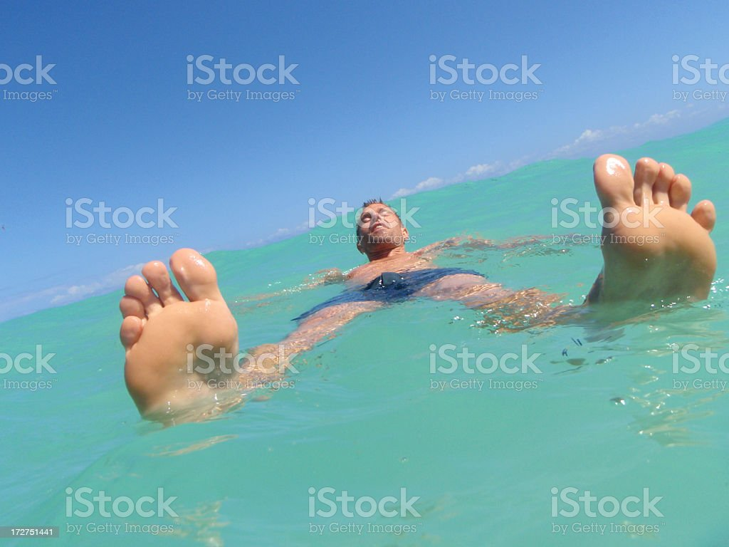 Guy and His Toes Float in Turquoise Seas royalty-free stock photo