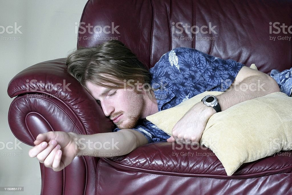 Guy asleep on the couch stock photo