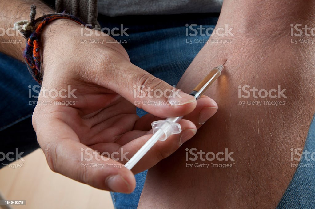 Guy busy injecting drugs into his system royalty-free stock photo