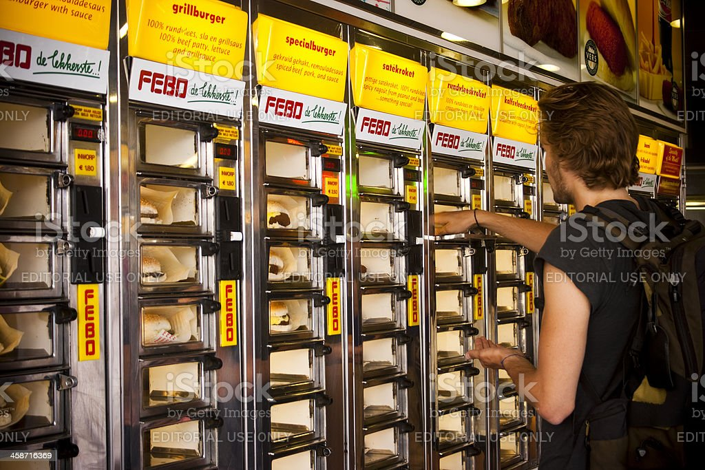 Guy buying burger from vending machine royalty-free stock photo