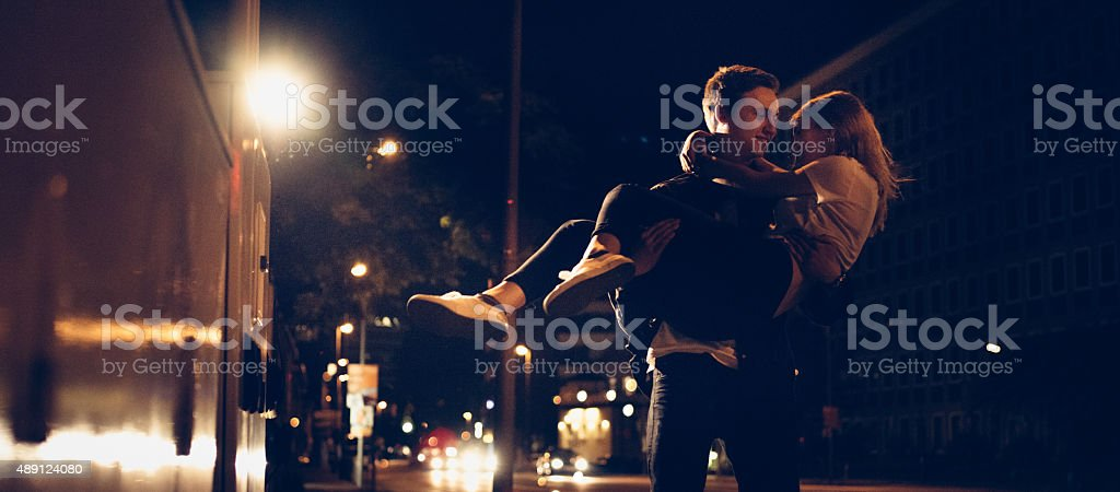 Guy carrying his girlfriend on an urban street at night stock photo