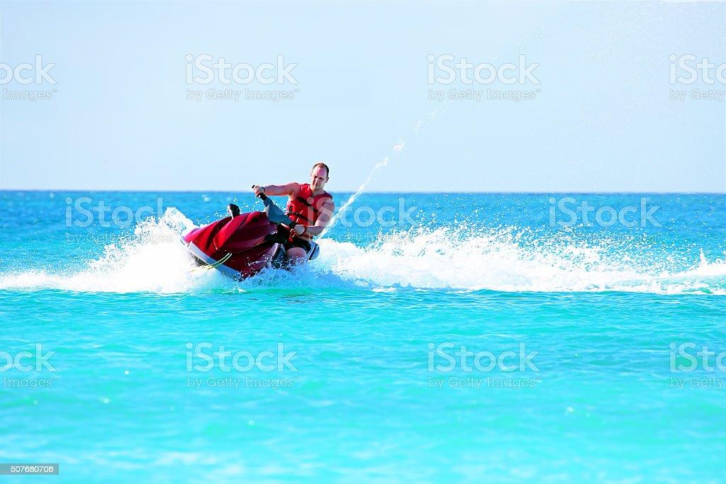 Guy cruising on a jet ski on the caribbean sea stock photo