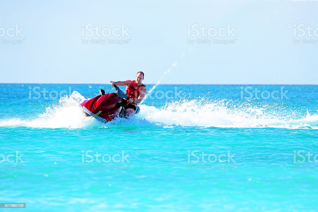 Guy cruising on a jet ski on the caribbean sea stock photo