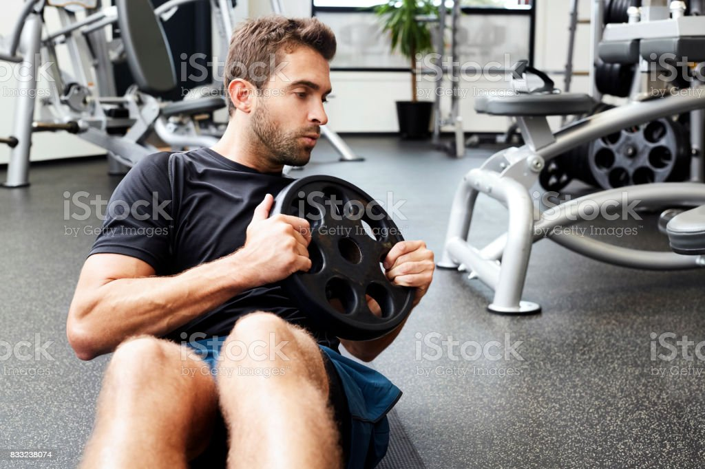 Guy crunching with weight stock photo