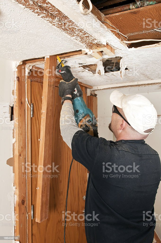 Guy cutting with saw stock photo