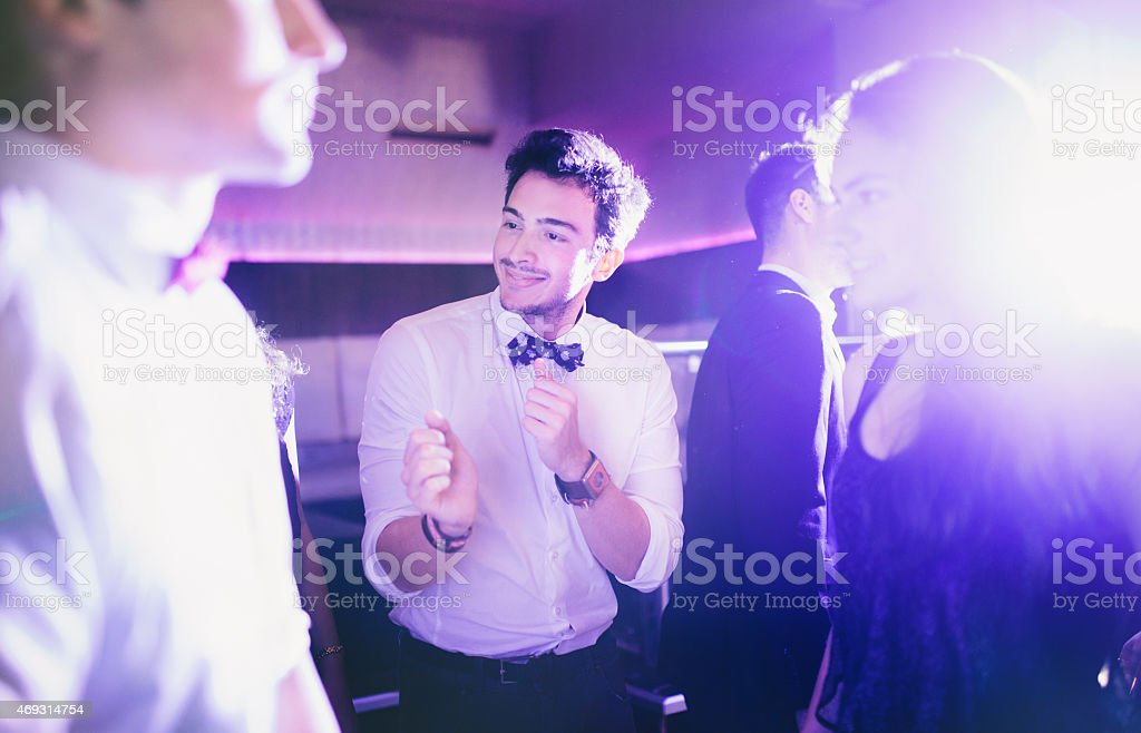 Guy dancing and having fun with friends on dance floor stock photo
