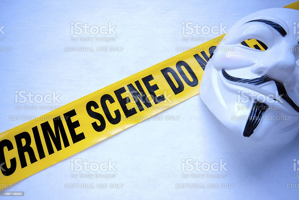 Guy Fawkes 'Anonymous' Mask And Crime Scene Tape stock photo