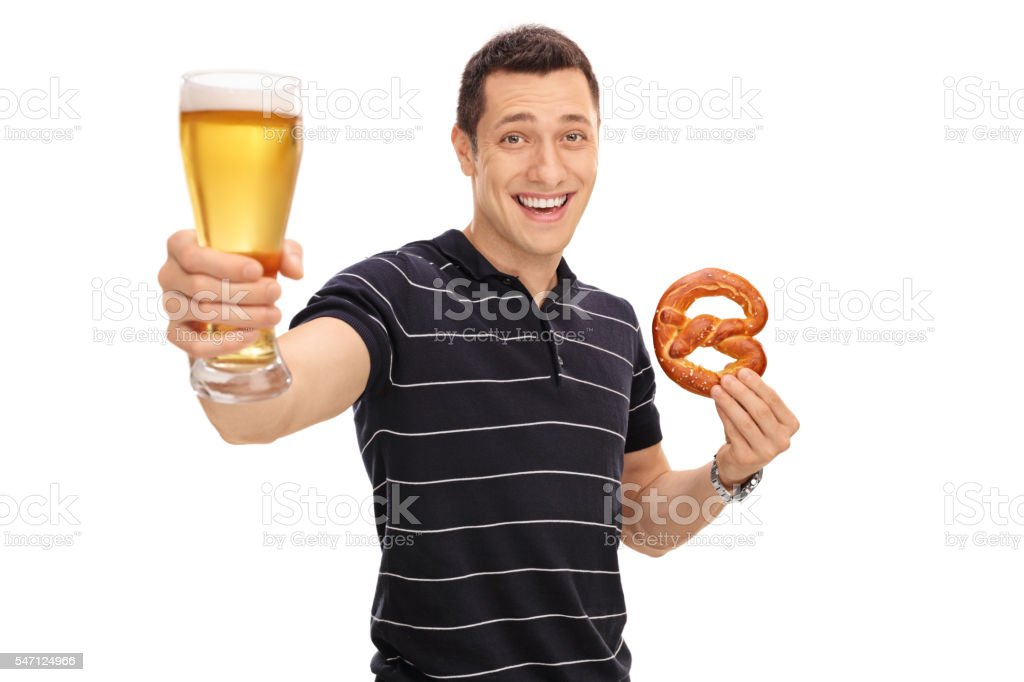 Guy holding a pretzel and a beer stock photo