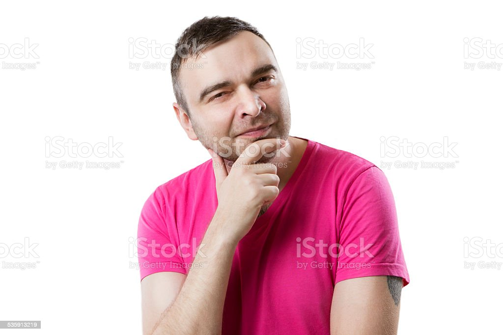 guy in a bright T-shirt squinting slyly looks stock photo