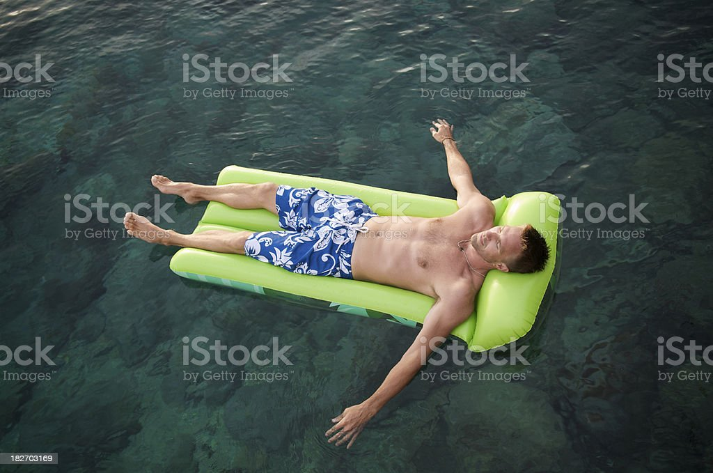 Guy in Green Lilo Floats on Emerald Waters royalty-free stock photo