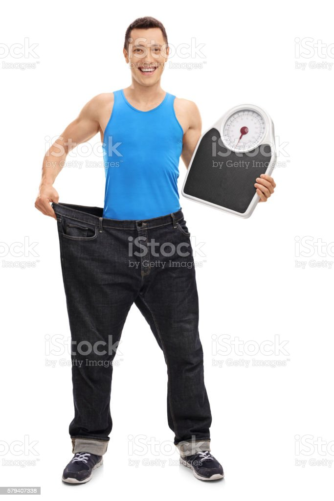 Guy in large jeans holding a weight scale stock photo