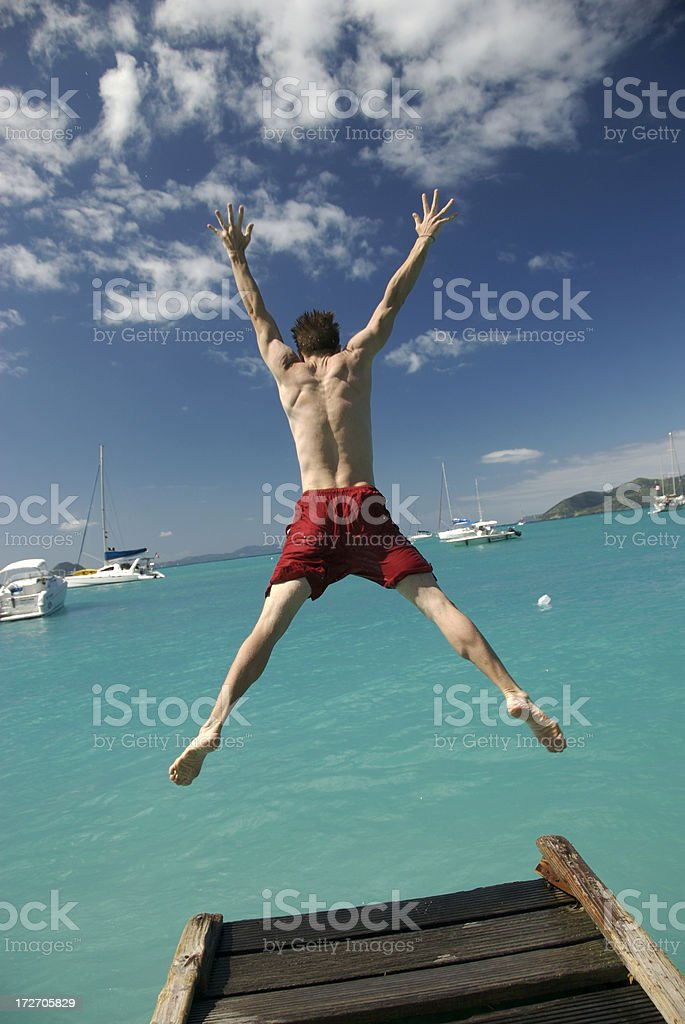 Guy in Red Shorts Makes Tropical Jump royalty-free stock photo