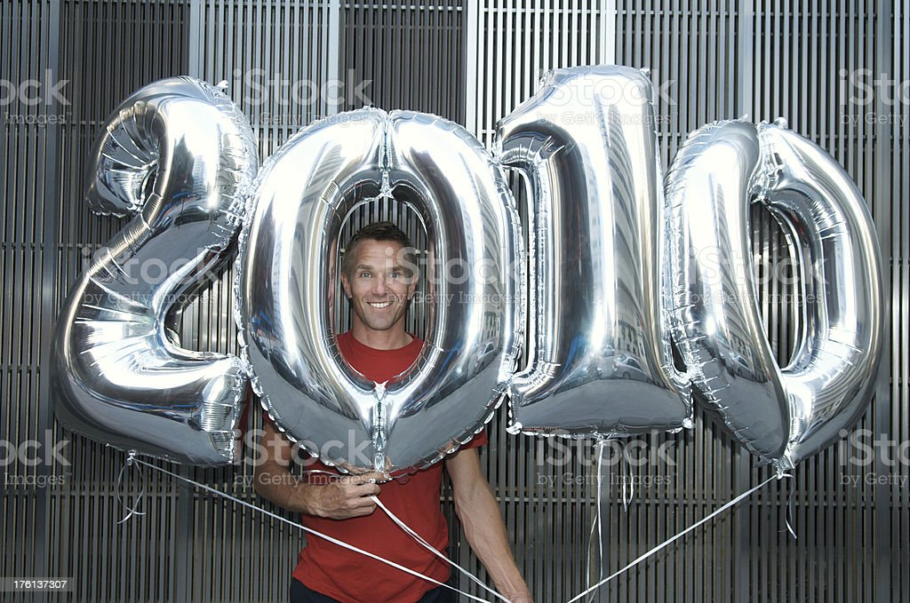 Guy in Red T-Shirt Holds 2010 Balloons royalty-free stock photo
