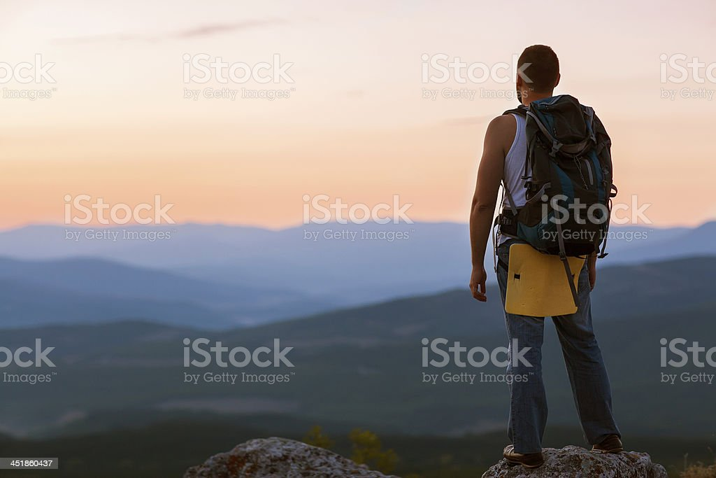 guy in the mountains at sunset. royalty-free stock photo