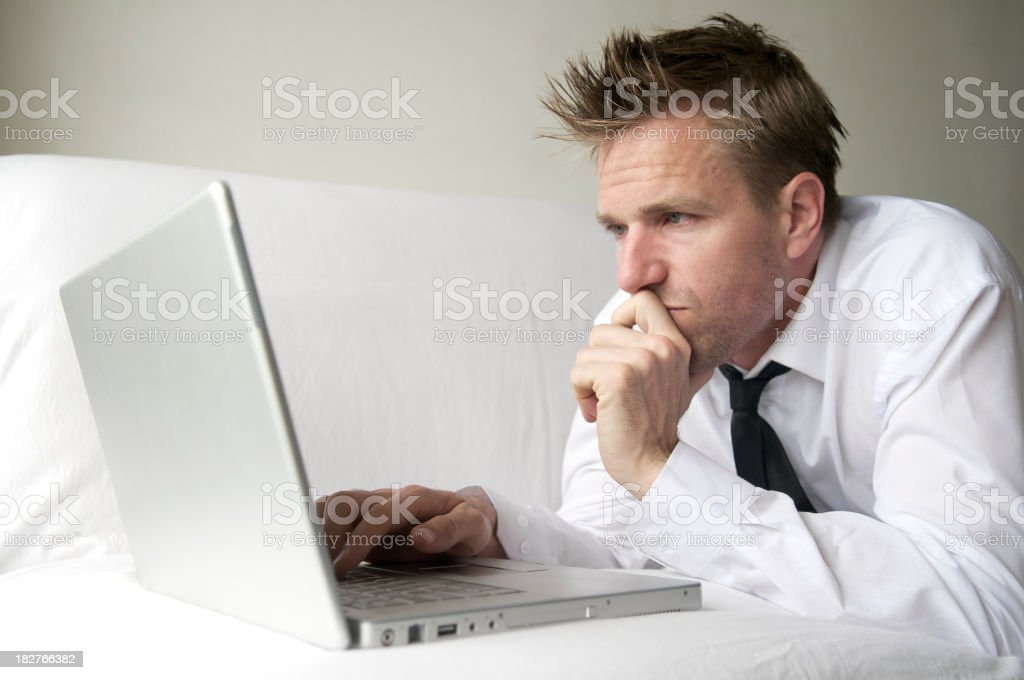 Guy in White Shirt and Black Tie Browses on Laptop stock photo