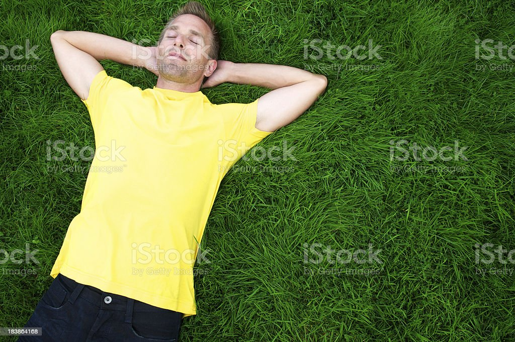 Guy in Yellow T-Shirt Lies w Eyes Closed Green Grass stock photo