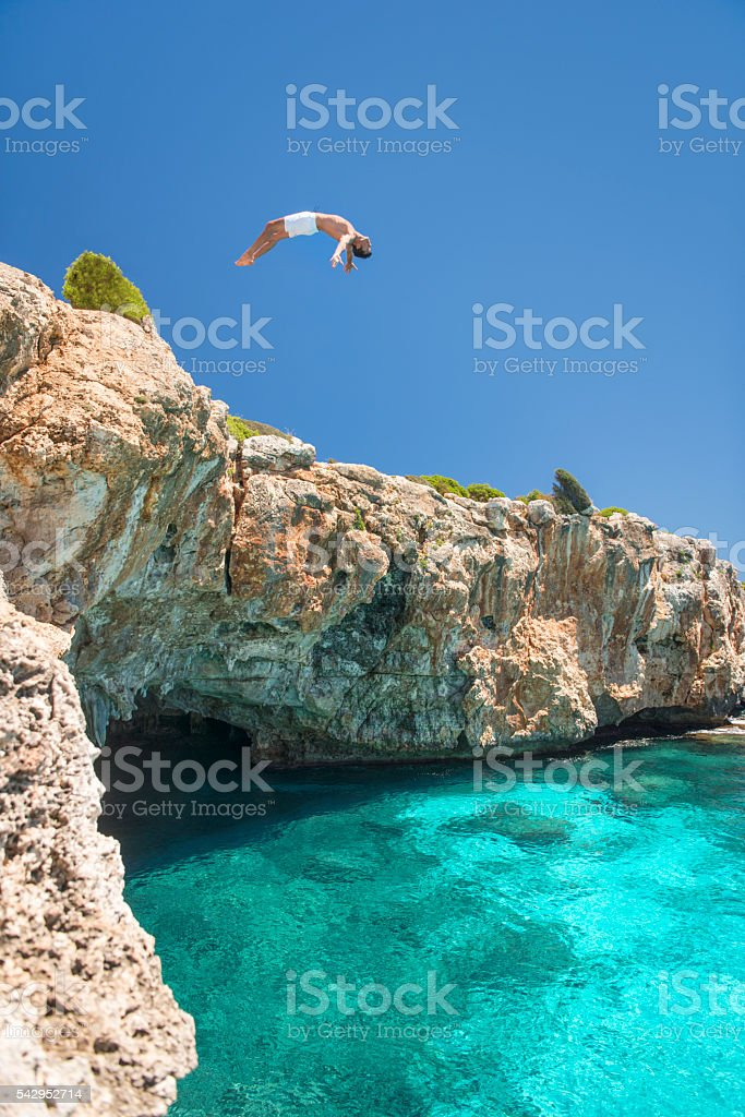 Guy jumping off a Cliff into the Ocean, Mallorca, Spain stock photo