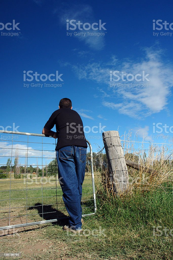 Guy leaning on fence stock photo