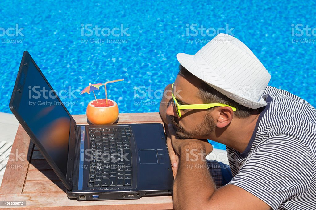 Guy looking at laptop screen at the poolside stock photo