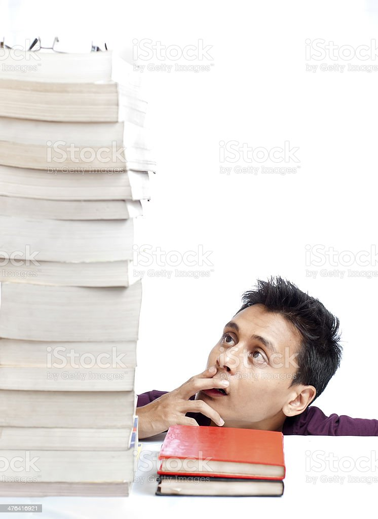 Guy Looking at the Tower of Books royalty-free stock photo