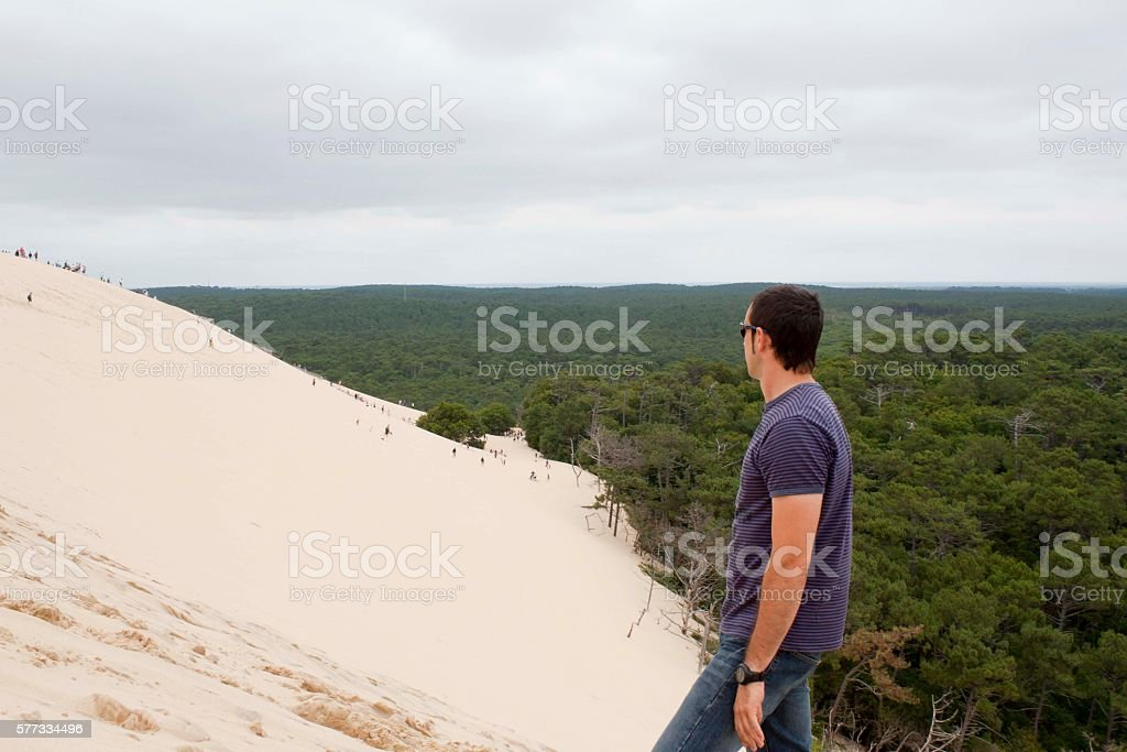 guy looking people going down the Pilat dune in France stock photo