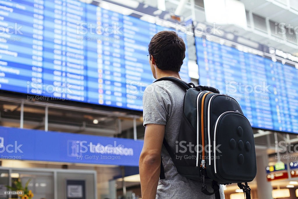 Guy near airline schedule stock photo