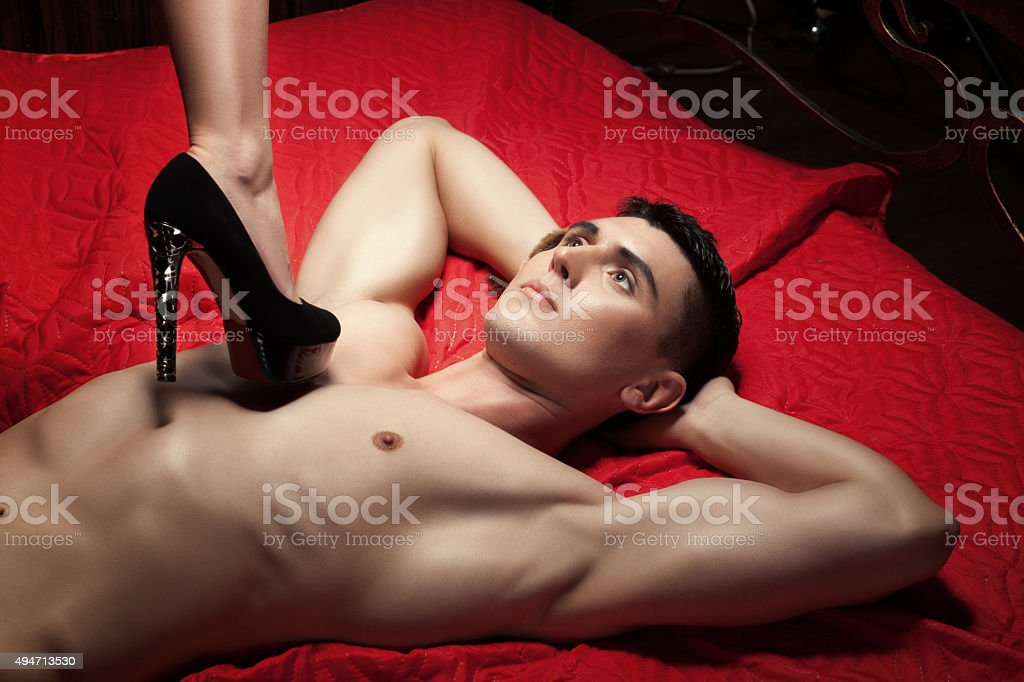 Guy on the chest is female foot in shoe heel. stock photo