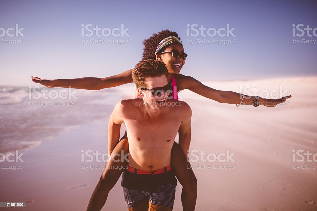 Guy piggybacking his Afro girlfriend who is pretending to fly stock photo