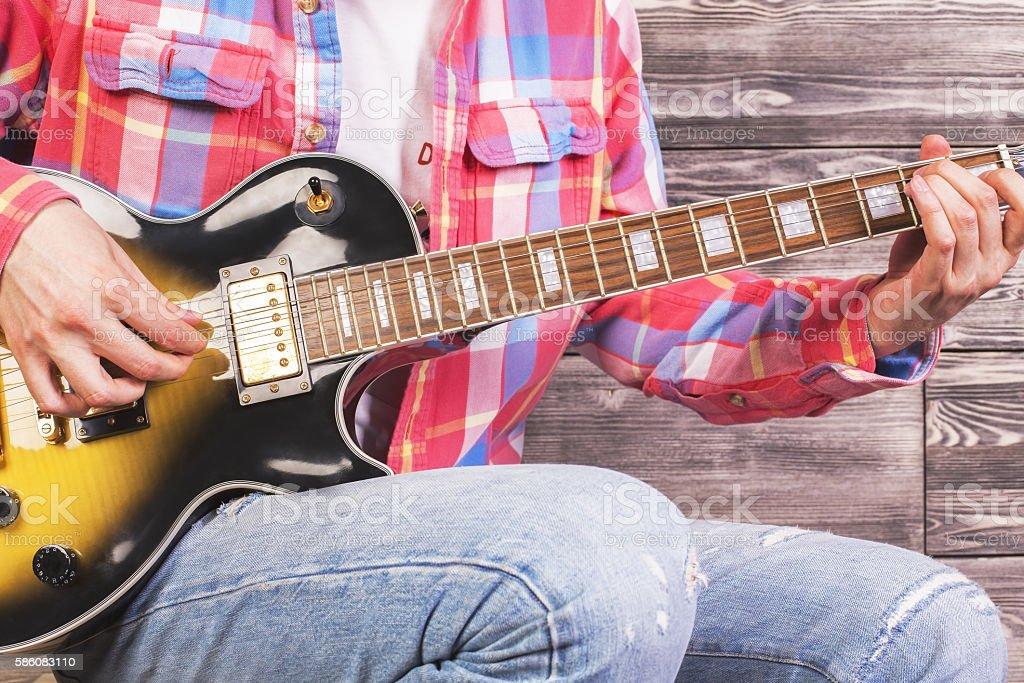 Guy playing guitar closeup stock photo