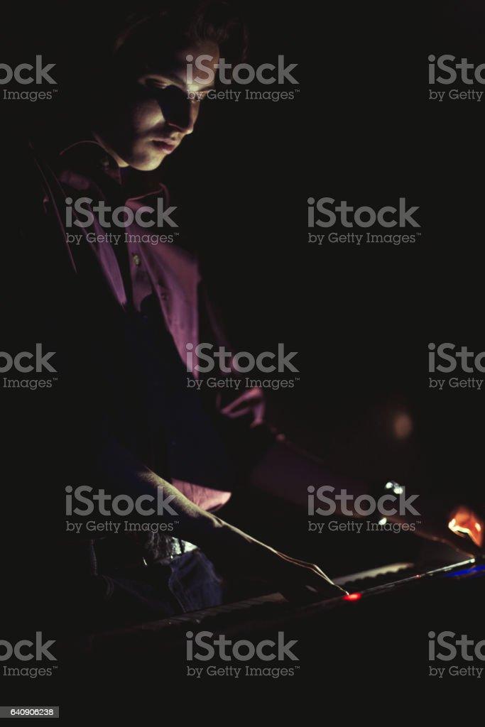 Guy playing on synthesizer keyboard stock photo